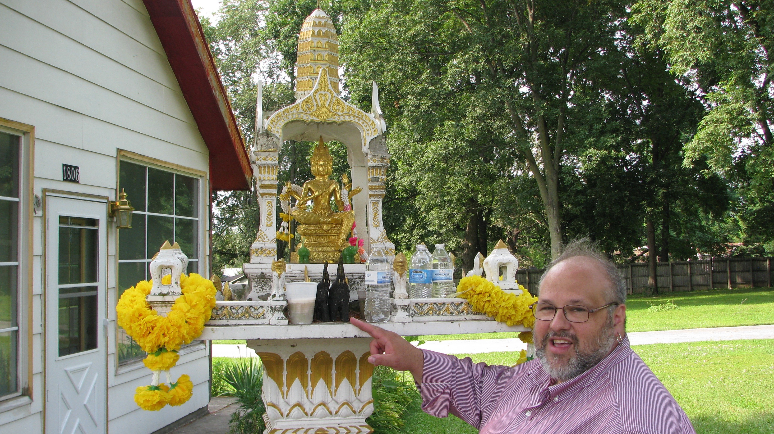 Dr. Christopher W. Chase discusses votive offerings left at a small shrine at Wat Lao Buddhavas, a Laotian Buddhist temple in Des Moines, IA.